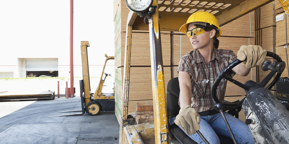 Female industrial worker looking away while driving forklift truck
